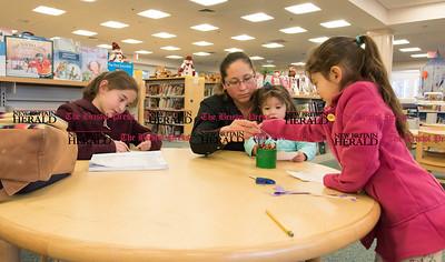 020617  Wesley Bunnell | Staff  Yecenia Rodriguez sits at a table in the Bristol Public Library on Monday Feb 6 as her daughters work on different projects. Rocxana Rodriguez, age 9 shown left, works on math problems, Fatima, age 1, sits on mom's lap as she helps Gabriella, age 4, with choosing crayons.