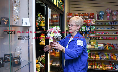 021717  Wesley Bunnell | Staff  Longtime volunteer at the Hospital of Central CT Kathleen Yuskis arranges flowers in the display case at the Auxiliary Gift Shop on Feb 17.