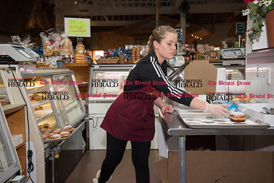 022317  Wesley Bunnell | Staff  Customers snapped up paczki as fast as Roly Poly Bakery could bring them to the counter on Fat Thursday Feb 23. Julia Jenny reaches for the last paczki on a tray fresh from the kitchen to stock the glass case.