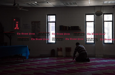 022317  Wesley Bunnell | Staff  Mayor Erin Stewart along with other city officials spoke at the Islamic Association of New Britain on Feb. 24 regarding her support for the Muslim community. A mosque worker prays along after the room has cleared.