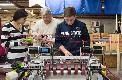 022317  Wesley Bunnell | Staff  The CyberKnights, Southington High School's robotics team aka FIRST Team 195, works on their prototype robots for the upcoming state competitions in space donated by Mohawk Northeast Inc. Electrical lead Natiya Washer, left, receives instruction from the electrical mentor Randy Bonomi with design lead Jake Hayes on the right.
