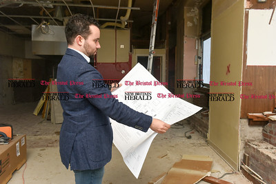 021517  Wesley Bunnell | Staff  Vincent Placeres looks over the plans for his restaurant which is soon to open at the corner of Main & West Main St. in New Britain. Mofongo Restaurant Is due to open in March.