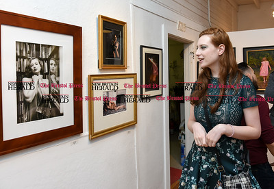 021717  Wesley Bunnell | Staff  Model Sarah Oppenheim looks over a photograph featuring her during The Art League of New Britain's show titled Love is All Around held on Friday Feb 17.