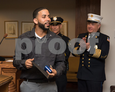 "022217  Wesley Bunnell | Staff  Juan ""Gaby"" Busanet received awards and recognition before the New Britain Common Council meeting on Feb 22. Busanet helped to rescue several residents of a burning building by climbing a ladder to the third floor of a burning building on West St. during a heavy snowstorm on Feb 9. Gaby Busanet gathers his awards at the end of the ceremony as Police Chief Wardwell and Fire Chief Ronalter applaud."