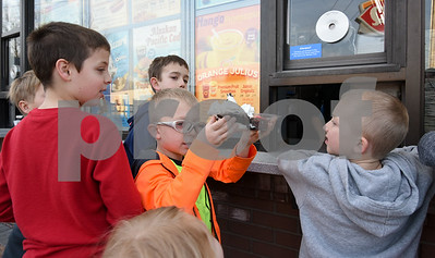 022217  Wesley Bunnell | Staff  All eyes are on the prize as Dylan Brini hoists his sundae as friends and family wait for their orders on the first day of business for Dairy Queen in Berlin for 2017 on Feb. 22. From left are Sam Monsonis, age 10, Noah Melyk, age 10, Dylan Brini, age 8, and Parker Brini age 6.