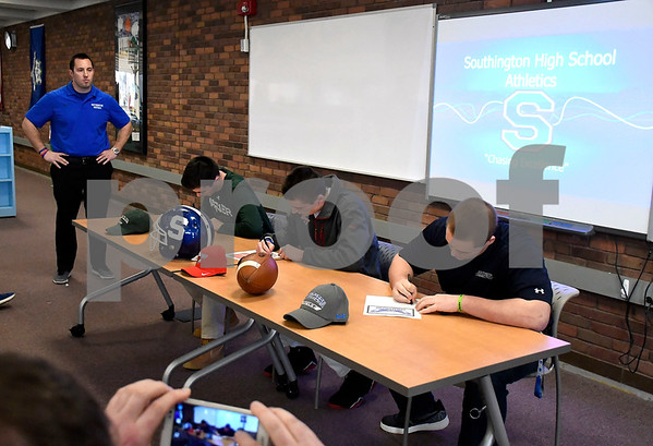2/9/2018 Mike Orazzi | Staff Southington High School Football Coach Southington looks on as Tim O'Shea, Sam Thomson and James Starr sign their letters of intent to play football at the next level during a ceremony at Southington High School Friday afternoon.