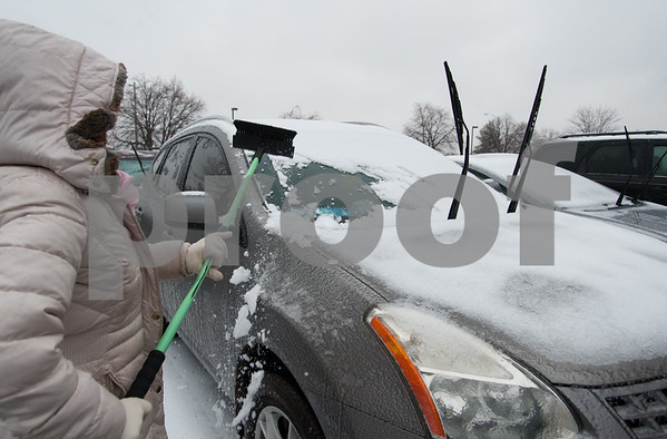 02/07/18 Wesley Bunnell | Staff Mayra Disdiel cleans her car off Wednesday afternoon in downtown New Britain as the snow started to give way to rain and ice.