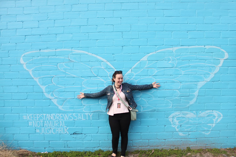 A girl stands in front of a blue wall with white wings painted on it, arms outstretched