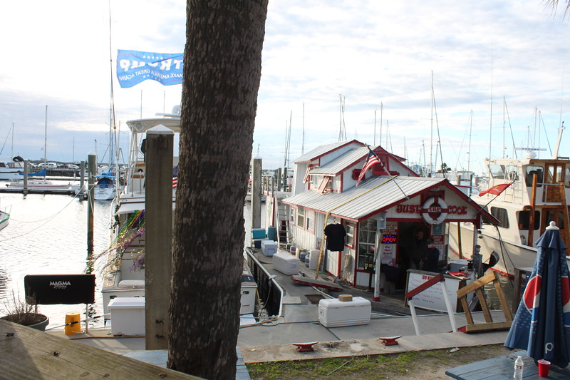 A row of boats sit in a marina, including one that is set up as a restaurant