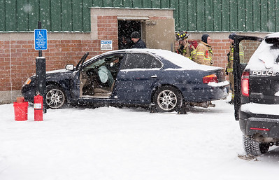 02/012/19  Wesley Bunnell | Staff  First responders stand next to a car which struck the rear of a building at 255 Myrtle St during a snow storm on Tuesday afternoon.