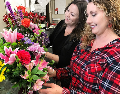 KEVIN HARVISON | Staff photo Pictured form left, Dana Ragan, Floral Designer and Tina Oliver, Floral Designer both of Foster's Flowers work on Valentine arrangements. Occording to an article Rebecca Lehmann wrote an estimated 250 million roses are grown for Valentine's Day every year and there is only 24 hours to deliver. Flowers must be planted and grown, well ahead of the February demand. Growers need 50-70 days to produce enough roses for Valentine's demand.