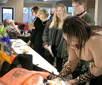 KEVIN HARVISON | Staff photo Shelli Colbert, far right, places a bid in the silent acution during the Pride In McAlester 10th Annual Volunteer Appreaciation Banquet Thursday at the McAlester Country Club.