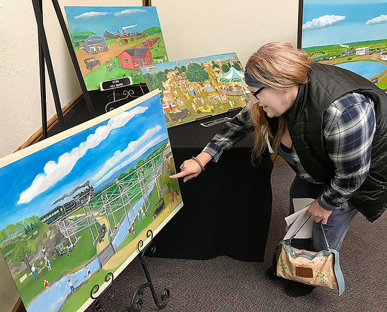 KEVIN HARVISON | Staff photo<br /> Catherine Bailey looks over some Oklahoma Folk Art at the Pittsburg County Library Tuesday evening.