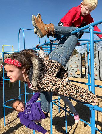 KEVIN HARVISON | Staff photo<br /> Emily Bryson, left , hangs around and watches as Maysen Carlton, center and Max Phillips, top right, play on the monkey bars.