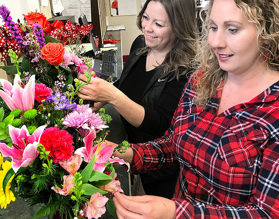 KEVIN HARVISON | Staff photo<br /> Pictured form left, Dana Ragan, Floral Designer and Tina Oliver, Floral Designer both of Foster's Flowers work on Valentine arrangements. Occording to an article Rebecca Lehmann wrote an estimated 250 million roses are grown for Valentine's Day every year and there is only 24 hours to deliver. Flowers must be planted and grown, well ahead of the February demand. Growers need 50-70 days to produce enough roses for Valentine's demand.