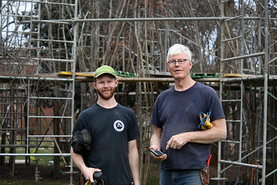 Artist Patrick Dougherty (right) and his son Sam stand in front of scaffolding that will be used during the 3-week installation process at the college.