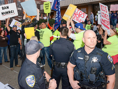 Chico Police Sgt. Dane Gregory, front right, stands guard as anti- and pro-needle distribution protesters clash Tuesday outside the Chico City Council Chambers in Chico. (Matt Bates -- Enterprise-Record)