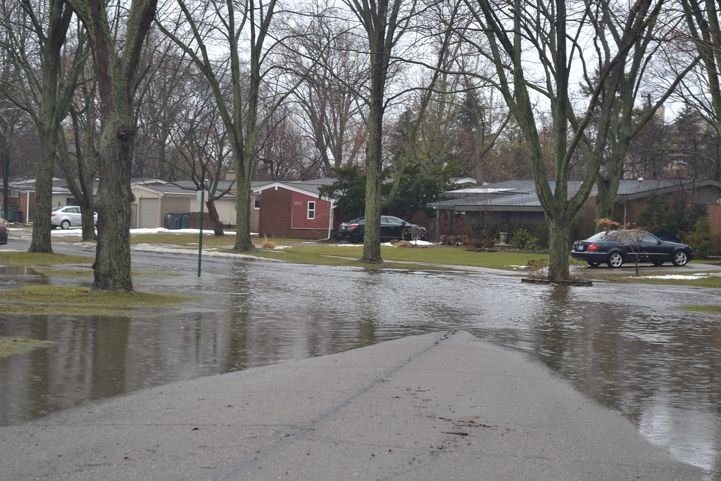 . A neighborhood street is flooded in Troy, near Big Beaver and Adams roads. Anne Runkle / Digital First Media.