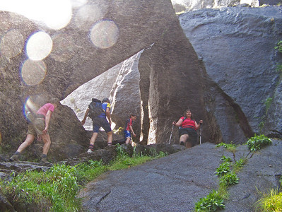 "The trail we are on is called the ""Mist Trail.""  As the water from the waterfall is falling, the mist blows across the trail.  You can see the ""rain"" blowing across the picture.  By this point, everyone on the trail is pretty much soaked.  The cool mist made the steep climb much more pleasant.  Pam is standing by a rock archway.  When you step through that arcway . . ."
