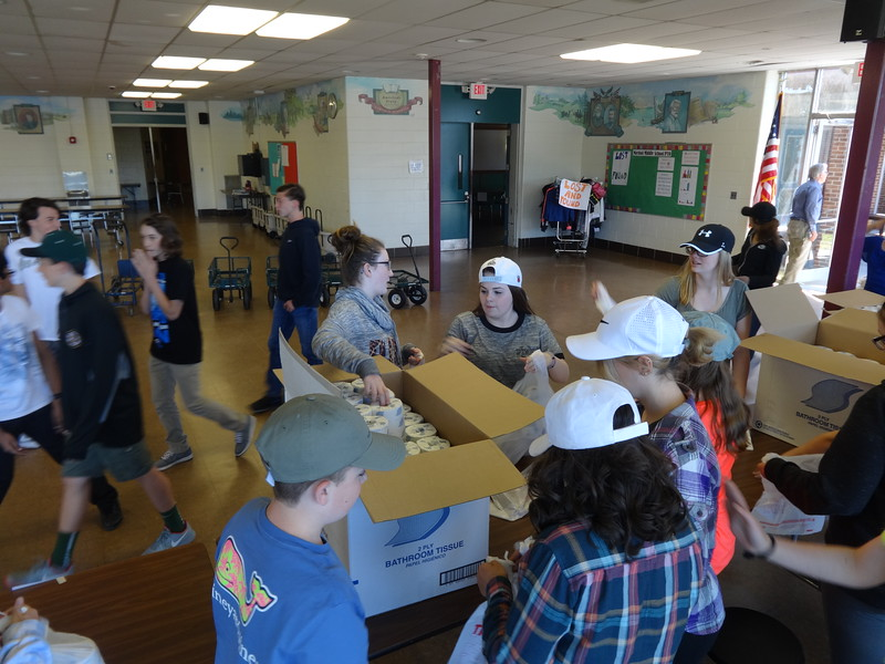 The Marshall Middle School cafeteria is full of activity as students, volunteers and teachers set up the food market. – photo by Mary