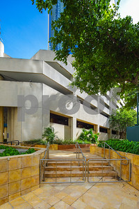 Vertical photo generic office building exterior with landscape plants and trees