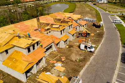 Aerial photo workers building townhomes roof assembly