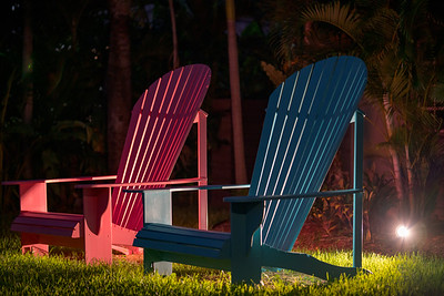Blue and red oversized lawn chairs at night