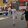 After introductions of the fencers, Katharine walks to the red strip accompanied by her referee (and the helper carrying the equipment of the fencers).