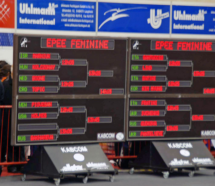 The round of 32 is displayed on boards at each end of the venue listing approximate start times for each of the bouts.
