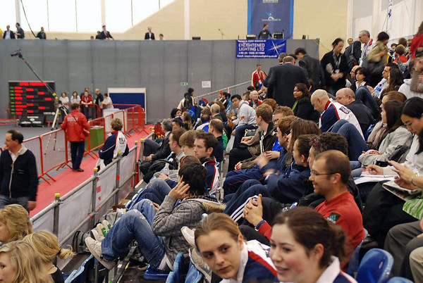 The audience gathers for the semi-final and final bouts.  Coach Jean Finkleman waits in the center to go to the coach's box.  Grace Neveu and Sarah Collins watch.