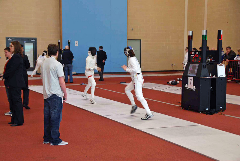 Katharine Holmes (right) vs. Jagoda Zagala (Poland).  The fencers' photos were displayed on the monitor so that the referee could be sure to have the correct fencers on strip.