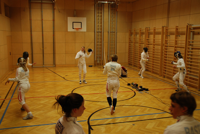 At the Club Balmung practice, Annie Stephenson is fencing on the left, Channing Foster in the center, and Katharine Holmes on the right.  Ashley Severson converses with one of the Austrian fencers.
