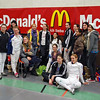 Some of the US fencers gather for a photo in front of the competition sponsor's display.