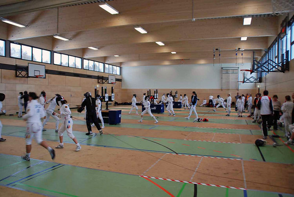 Fencers warming up before the start of pools on the first day of the competition.  This is the upstairs gymnasium.  Four rooms were used in this building, plus a gymnasium at a nearby school for the 247 entries in the competition.