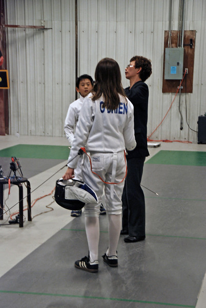The referee checks the weapons before Alex Wang and Elizabeth O'Brien compete.