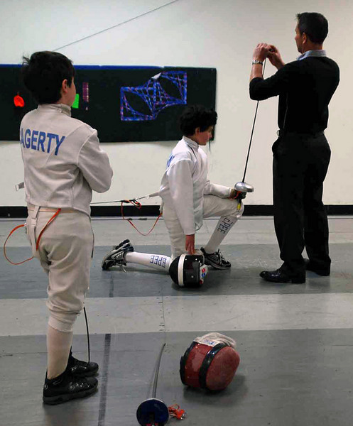 Levi Freedman has his epee checked by the referee as Rory Hagerty looks on.