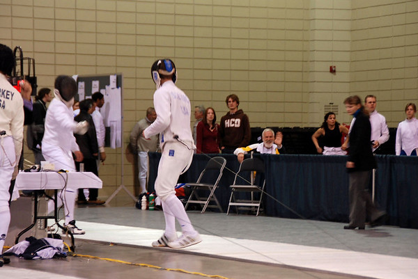 Bill Reith, seated, waves to the camera while watching his student Ben Solomon fence.