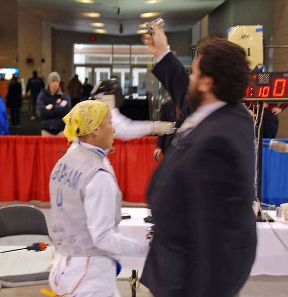 The referee checks the tip weight on Bettie Graham's foil in the Veteran 60+ Women's Foil.