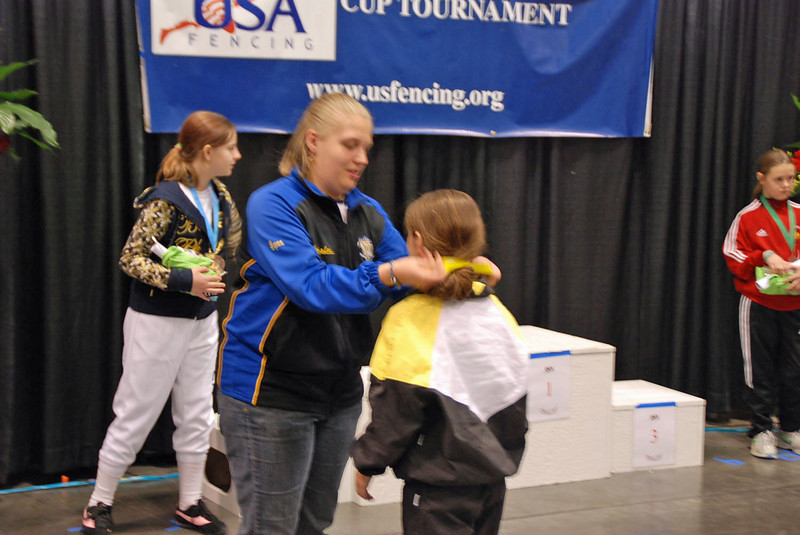Elizabeth Wiggins receives the 5th place medal from one of the members of the local organizing committee.