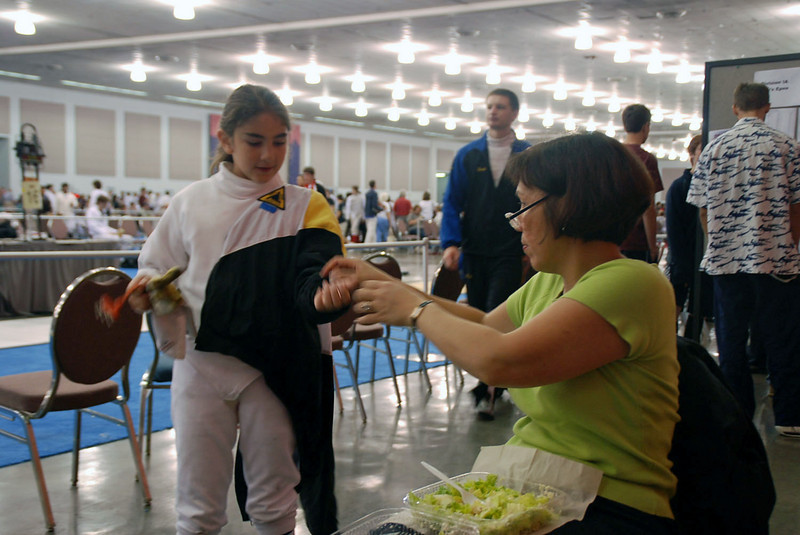 Elizabeth Wiggins' mom, Rebecca, helps her get ready for the Youth-10 Women's Epee.
