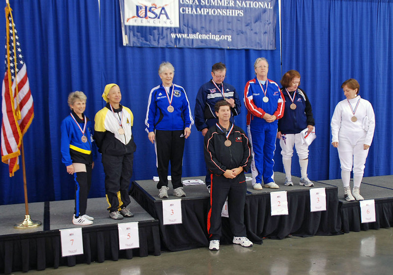 The finalists of the Veteran-60 Women's Foil, from left: Judith Evans (7th), Bettie Graham (5th), Ellen O'Leary (3rd), Linda Nowell (1st), Patricia Bedrosian (2nd), Diane Reckling (3rd), and Anna Mannino (6th).  Linda Nowell's coach receives the Coach's Medal.