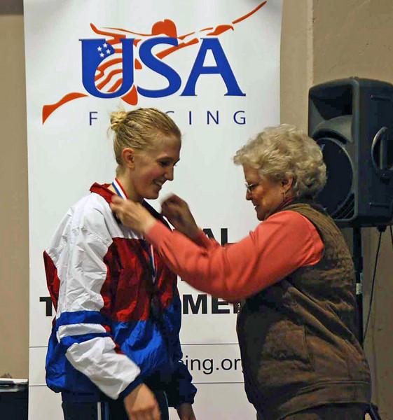 Oksana Samorodov receives her 5th place medal in Cadet Women's Epee from Nancy Anderson.