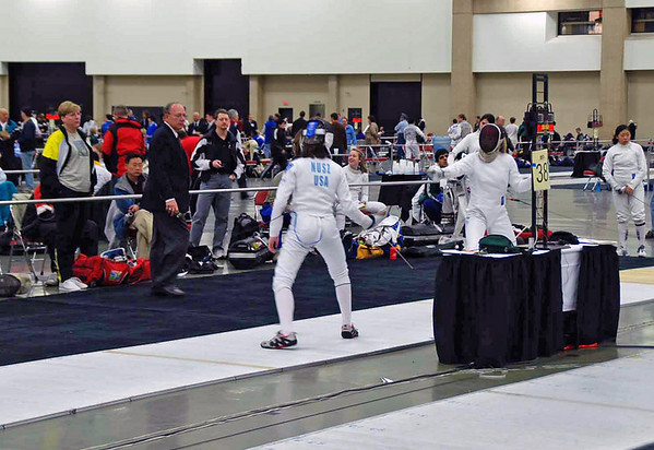 Coach Jean Finkleman watches Channing Foster (right) fencing Juleah Nusz in the Junior Women's Epee.