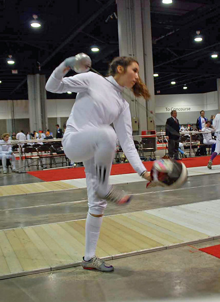 Ella Barnes uses her foot to pick up her mask at the start of the Division III Women's Epee.