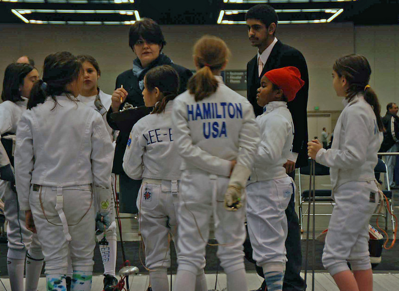 The referees gather the fencers together for the Y10 Women's Epee.