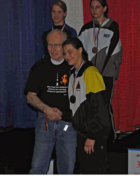 Katharine Holmes receives her third place medal U19 Women's Eepee from Joe Byrnes, head armorer.