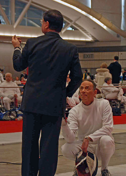 Referee Jerry Benson inspects Mark Henry's epee in the Veteran-60 Men's Epee.