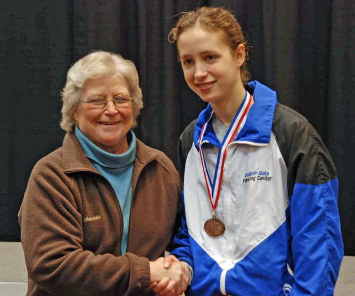 Hannah Safford receives her 3rd place medal in Junior Women's Epee from Nancy Anderson, former president of the USFA.