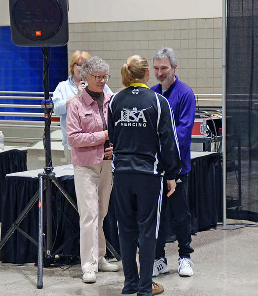 Channing Foster receives her 5th place medal in Cadet Women's Epee from Ro Solbarvarro, national women's epee coach.  Channing earned her A rating.