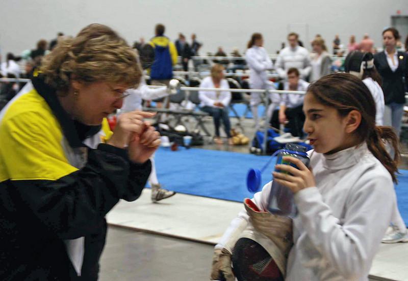 Coach Jean Finkleman talks to Elizabeth Wiggins during the 1-minute break in her Y14 Women's Epee DE bout.